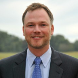 man wearing a blue tie and suit outside